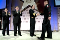 U.S. Navy Adm. Mike Mullen, chairman of the Joint Chiefs of Staff, congratulates U.S Navy Petty Officer 2nd Class William S. Stevens as the USO Sailor of the Year at the 2009 USO Gala at the Marriott Wardman Park, Washington, D.C., Oct. 7, 2009, as USO President and CEO Sloan Gibson, left, and USO Chairman of Board of Governors Edward T. Reilly applaud. DoD photo by U.S. Navy Petty Officer 1st Class Chad J. McNeeley