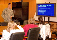 Capt. Josh Metz, a chaplain with U.S. Army Garrison Wiesbaden Religious Services Office, talks about the benefits of military life during a Spouse Battlemind training session with spouses of Special Troops Battalion, 1st Armored Division, Soldiers.